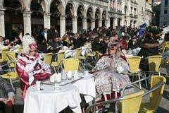 Turistas y personas enmascaradas en el traje colorido que se sienta en café Foto de archivo libre de regalías