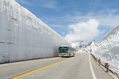 Turistbussen fortskrider väggen för Japan fjällängsnö på den alpina rutten för tateyama kurobe Arkivfoton