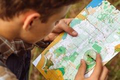 Turisten bestämmer den ruttöversikten och kompasset Fotografering för Bildbyråer