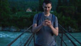 Turisten fotograferar en vän på en mobiltelefon lager videofilmer