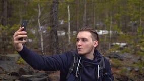 Turisten fotograferar sig på en mobiltelefon i skogen lager videofilmer