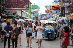 Turisten går och tuktuktaxien på den Khao San vägen, Bangkok, Thailand royaltyfria bilder