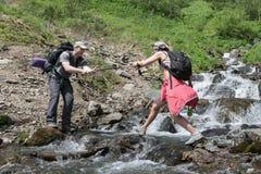 Turisten hjälper enturist till att korsa bergfloden Arkivbild