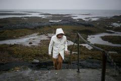 Turisten i den vita regnrocken går på den Island kusten arkivbild