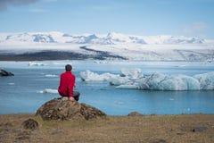 Turisten i ett rött omslag sitter på kusterna av den is- lagun royaltyfri foto