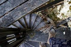 Turisten i kängor går på en gammal träspiraltrappuppgång royaltyfria foton