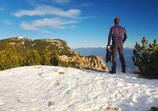 Turisten i svart står på stenig siktspunkt och håller ögonen på in i dimmiga steniga berg Kufvintermorgon i fjällängar Arkivfoton
