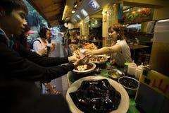 Turisten köper exponeringsglasgelé från gatamat stannar i Taiwan arkivbild