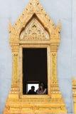 Turisten låser fast ett foto från ett utsmyckat fönster av Wat Traimit, ett I arkivfoto