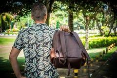 Turisten med den stilfulla bruna snakeskinpytonormryggsäcken i asiatet parkerar bali indonesia Stilig caucasian man in Royaltyfri Fotografi