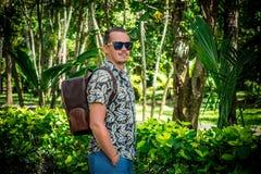 Turisten med den stilfulla bruna snakeskinpytonormryggsäcken i asiatet parkerar bali indonesia Stilig caucasian man in Royaltyfri Foto