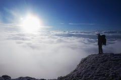 Turisten med den stora ryggsäcken står på siktspunkt och håller ögonen på in i den dimmiga dalen solig vinter för morgon Arkivbilder