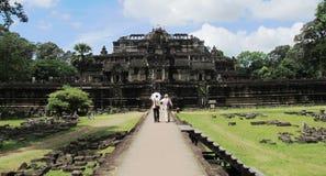 Turisten och handboken går till en tempel på det Angkor komplexet, Cambodja arkivbilder
