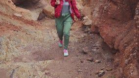 Turisten promenerar den bergiga terrängen Handelsresande för ung kvinna med ryggsäcken röd jord och berg, som på arkivfilmer