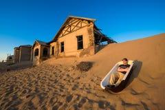 Turisten sitter i ett badkar i den Kolmanskop spökstaden, Namibia royaltyfri foto