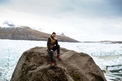 Turisten sitter nära glaciärisberget i Island royaltyfri fotografi