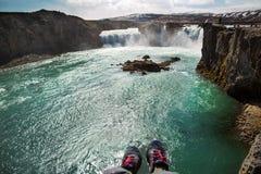 Turisten sitter på en klippa nära floden som ner hänger hans ben, v arkivbild