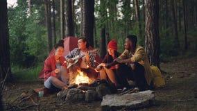 Turisten spelar gitarren som sitter nära lägereld med vänner som sjunger, och att ha gyckel, ungdomarrymmer pinnar arkivfilmer
