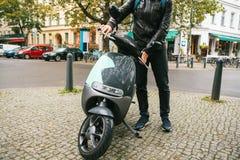 Turisten steg ombord en elektrisk sparkcykel Ett populärt medel i staden kallas en elektrisk sparkcykel I bakgrunden Royaltyfri Bild