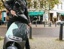 Turisten steg ombord en elektrisk sparkcykel Ett populärt medel i staden kallas en elektrisk sparkcykel I bakgrunden Arkivfoto