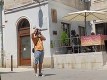 Turisten tar ett foto på gatan av Pula Arkivfoton