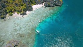 Turisten turnerar turbancafartyg i grunt vatten på Shimizu Island i El Nido, Palawan, Filippinerna Intakt korallrev arkivfilmer