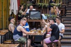 Turisten tycker om att dricka öl på den khaosan vägen arkivfoton