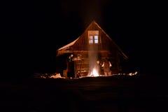 Turisten värmde vid brand på vintern nära en träkabin Arkivbild