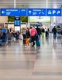 Turister ankommer på Prague den internationella flygplatsen som är klar att lämna flygplatsen och att starta deras ferier arkivfoto