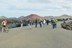 Turister bredvid den steniga kusten av Los Hervideros Arkivbild
