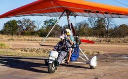 Turister för flyget över Victoria Falls på trikes Fotografering för Bildbyråer