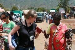 Turister för infödda erbjudanden för svart kvinna köper europeiska souvenirproduc Royaltyfri Bild