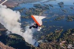 Turister flyger över Victoria Falls på trikesna Royaltyfri Foto
