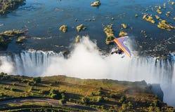Turister flyger över Victoria Falls på trikesna Fotografering för Bildbyråer