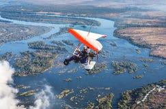 Turister flyger över Victoria Falls på trikesna Royaltyfria Foton