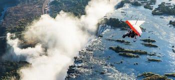 Turister flyger över Victoria Falls på trikesna Arkivbilder