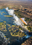 Turister flyger över Victoria Falls på trikesna Arkivfoton