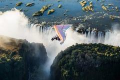 Turister flyger över Victoria Falls på trikesna Arkivfoto
