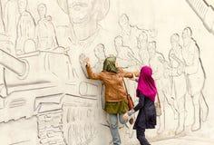 Turister från Asien poserar framme av diagram som beskriver bedrifter av Royaltyfria Bilder