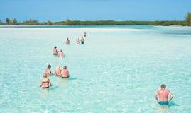 Turister går att vada för att undersöka ön. Cubaa Arkivbild