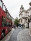 Turister går mellan linjer av bussar och St Pauls Cathedral på r royaltyfria foton