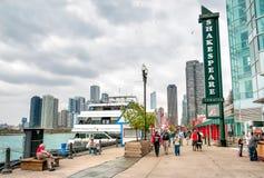Turister går nära den Shakespeare teatern som lokaliseras på den berömda marinen som pir parkerar i Chicago Arkivfoton