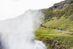 Turister går nära kanjonen av den Gullfoss vattenfallet Arkivbild