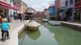 Turister går till gatan längs vattenkanalen med transport och färgar hus stock video