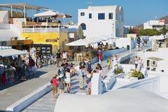 Turister går vid gatan i Oia, Grekland Arkivbilder