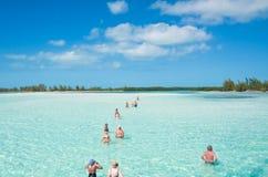 Turister går att vada till ön av Cayo Largo. Kuba Arkivbild
