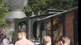 Turister i en gammal järnvägsstation som förbereder sig för en tur med ett drev för ångamotor stock video