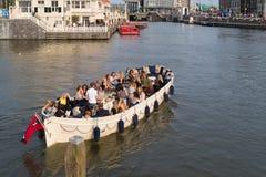 Turister i ett fartyg på en amsterdam kanal royaltyfri bild