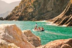 Turister i ett fartyg som beundrar landskapet av Cinque Terre Royaltyfria Foton