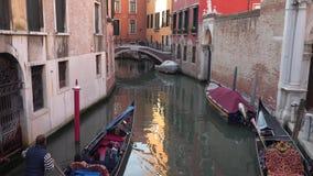 Turister i gondolerna simmar till och med de smala kanalerna i Venedig arkivfilmer